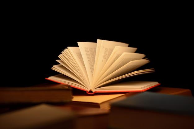 黒に対して金色の暖かい光に照らされた開いた本