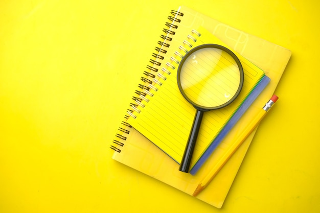 Open book and magnifying glass on yellow