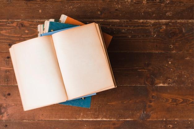 Open book over more books