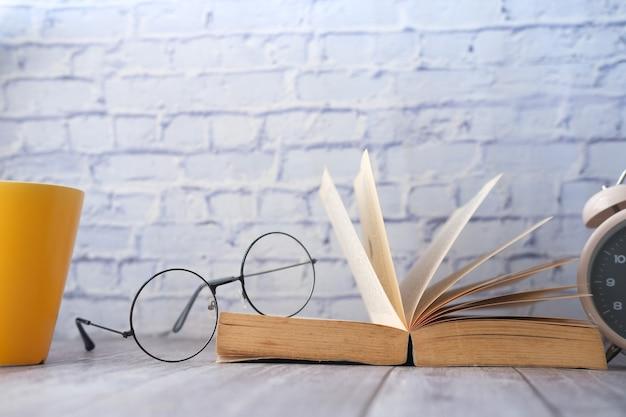 木製のテーブルに本のマグカップの眼鏡と鉛筆を開く