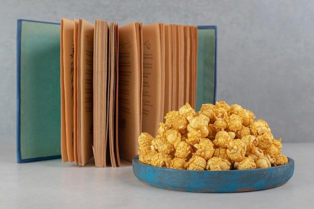 大理石のテーブルの上のキャラメルポップコーンのいっぱいになった小さなトレイの横にある本を開きます。