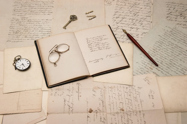 Open book over old letters and postcards