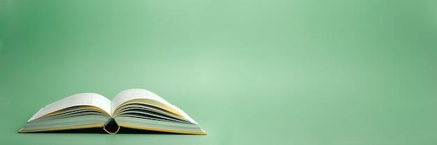 緑の背景で本を開く