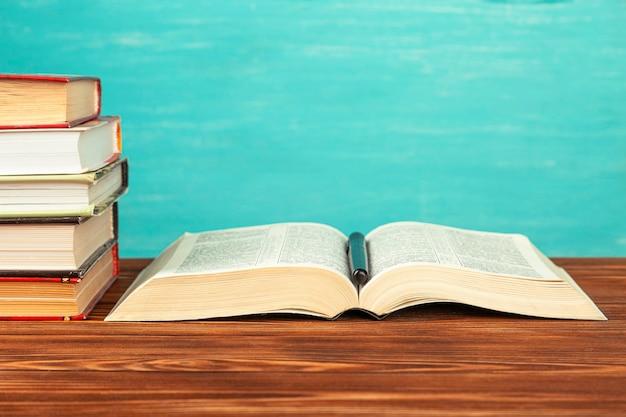 Открытая книга на стопке книг на столе. скопируйте пространство.