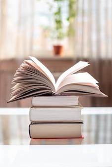 Раскройте книгу на стоге книг на таблице в светлой комнате. обучение и чтение бумажных книг