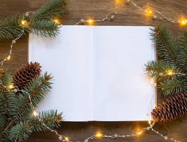 Открытая книга на деревянном столе с еловыми ветками и желтой гирляндой.