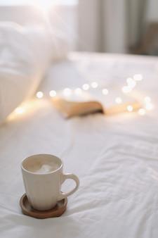 ベッドシーツと一杯のコーヒーで本を開き、ベッドで朝食
