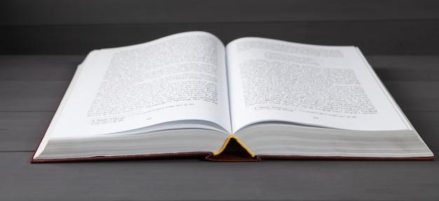 灰色の木製のテーブルに開いた本