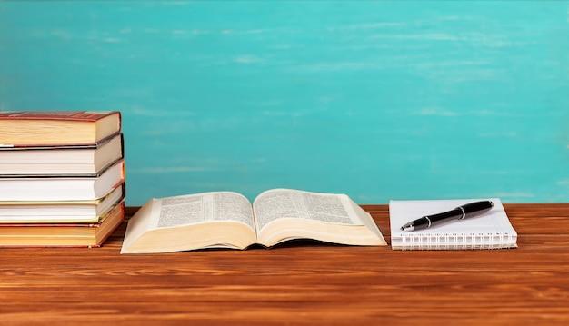 Открытая книга на столе, блокнот, ручка.