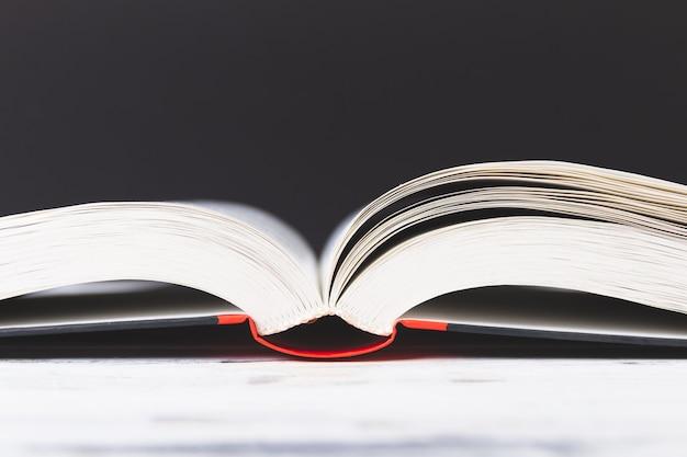 白いテーブルの上の本を開きます。製本の背景。教育コンセプト。