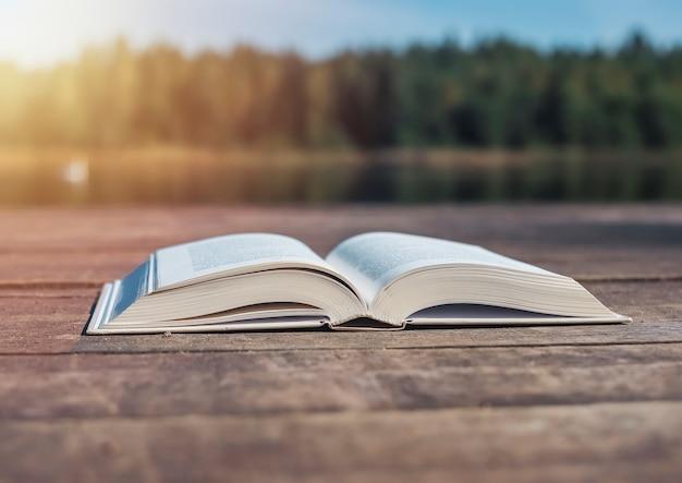 Открытая книга на деревянном столе в концепции летнего чтения природы