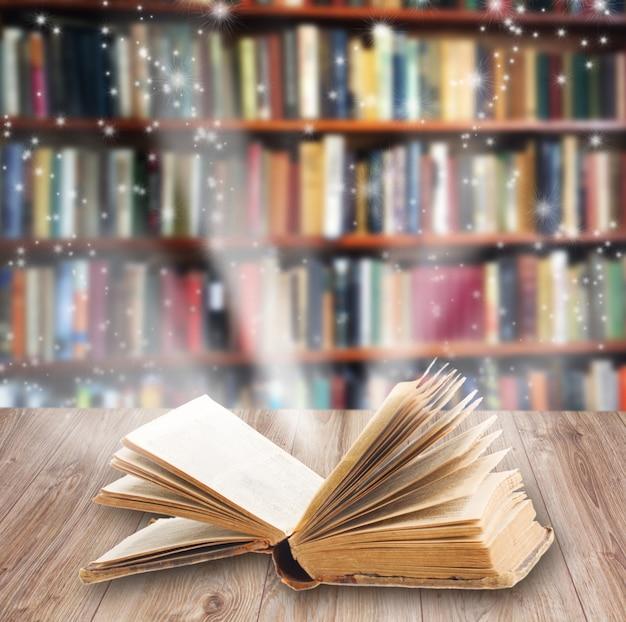 Открытая книга на деревянной книжной полке с волшебным светом