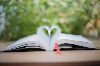 Open book on wooden table on natural background. Heart book page , blurry and soft focus