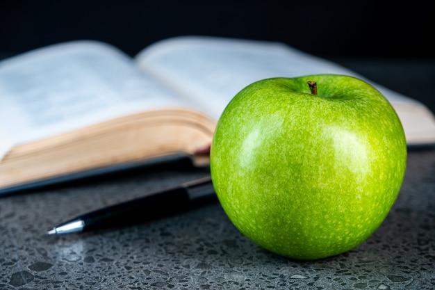 Открытая книга, ручка и зеленое яблоко на черном фоне, образование
