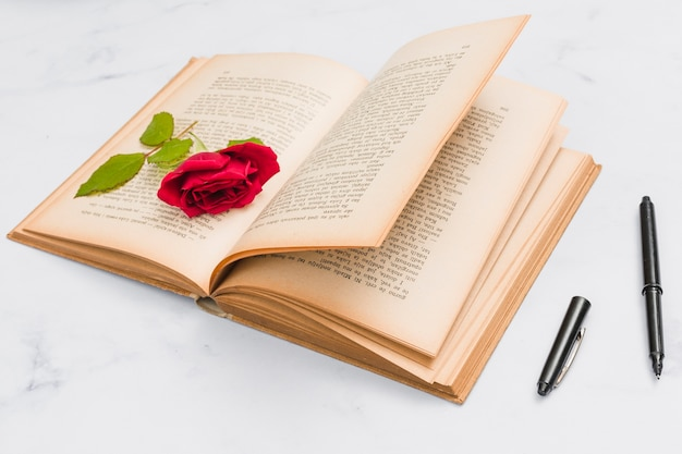 Open book, pen and rose