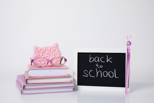 Открытая книжная стопка книг в розовых и фиолетовых обложках, очки, ручка, карандаш, линейка и рамка для доски