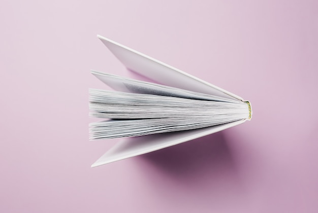 Open book on a pink surface
