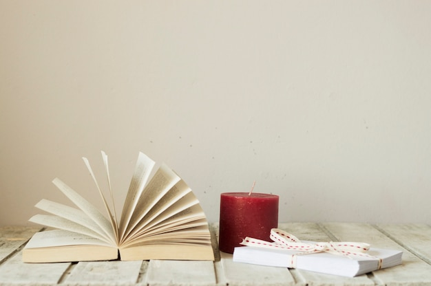 Open book, red candle and gift box