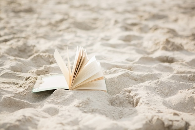Open book on sand