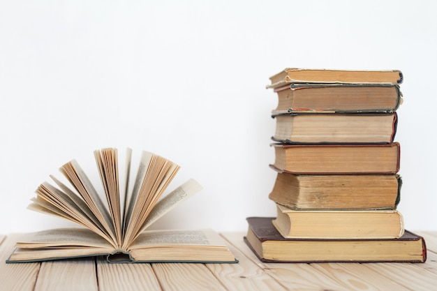 An open book next to a stack of vintage books on a wooden surface against a white wall.