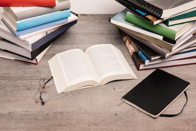 Apri il libro accanto a pile di libri