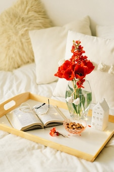 Open book and vase red tulips on a tray on the bed