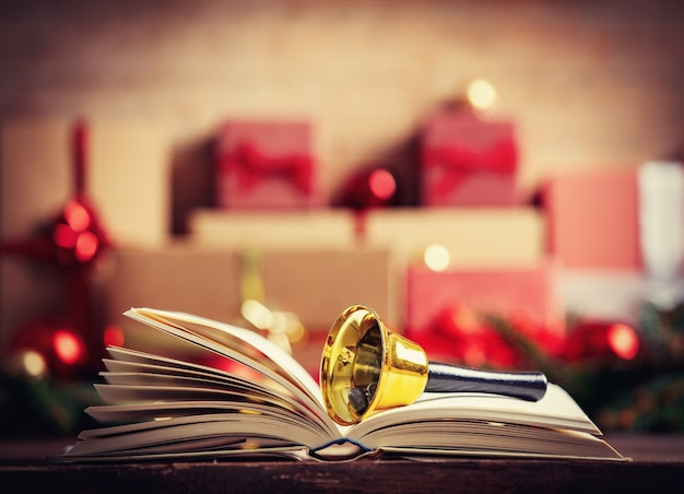 Open book with bell and christmas gift and baubles on background