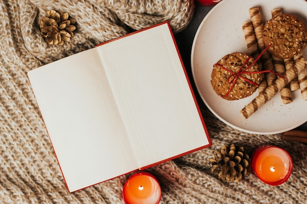 Open book with blank pages, cookies on a plate and candles on a knitted blanket