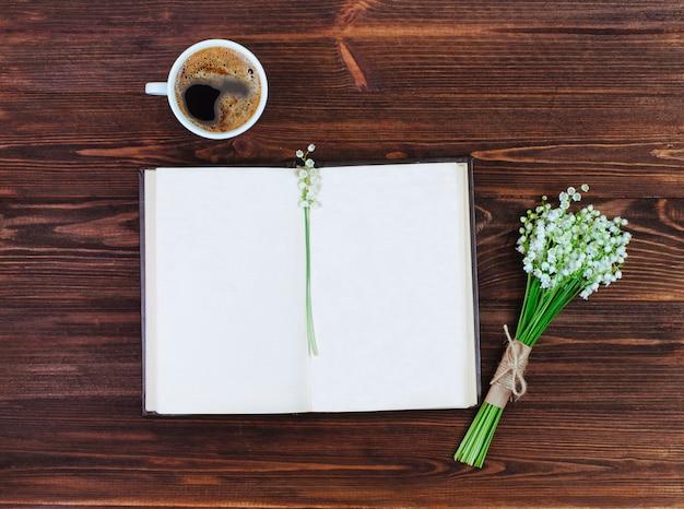 一杯のコーヒーとユリの花の近くのテキストを空白で開いた本