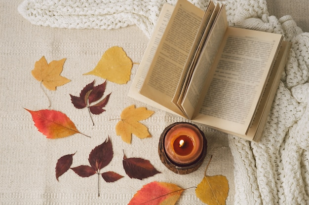 Open book with candles and leaves