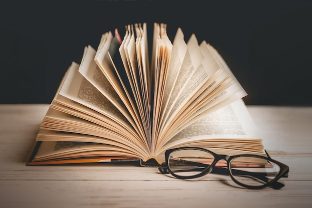 An open book with glasses on a wooden table against the background of a set of books, vintage toning.