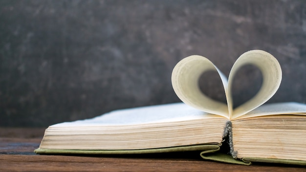 Open book with heart shape from paper page on dark wood table