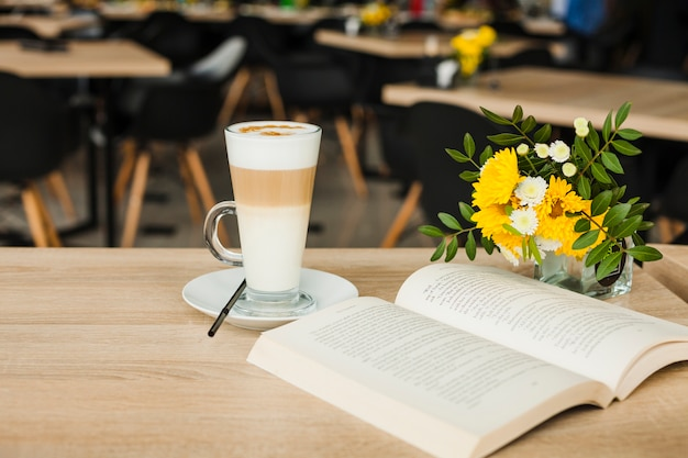 Open book with latte coffee cup and fresh flower vase over wooden table