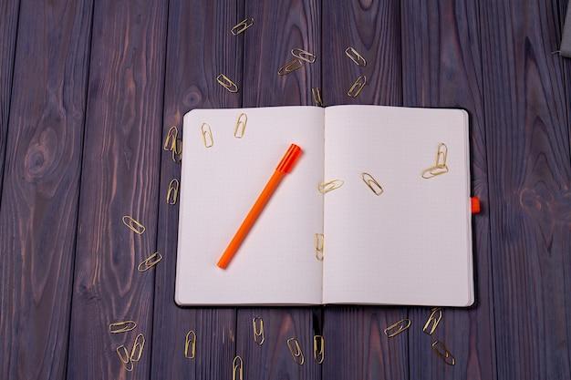 ペンとペーパークリップで本を開きます。素朴な暗い木製の机の背景。