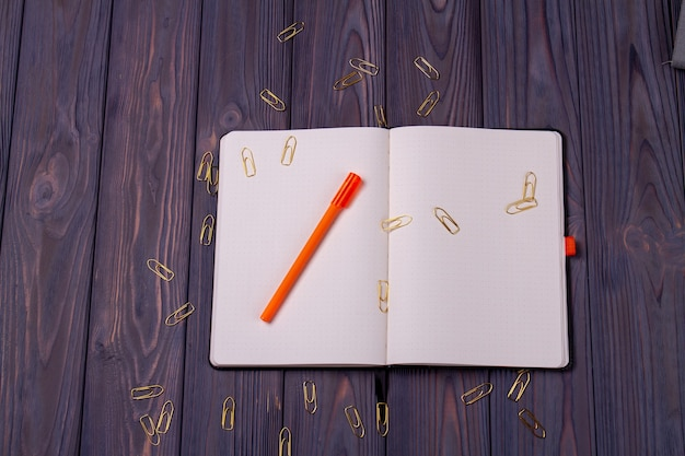 Open book with pen and paper clips. rustic dark wooden desk background.
