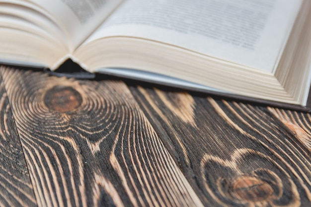 Open book on wooden desk close up.