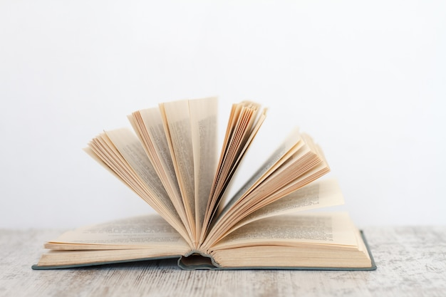 Open book on a wooden surface against the background of a white wall