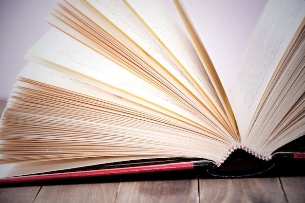 Open book on wooden table.