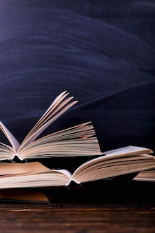 Open books are a stack on the desk, against the background of a chalk board