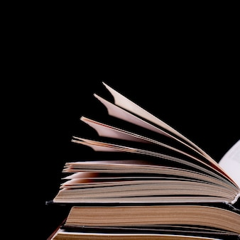 Open books are stacked on the desk, on a black background, isolate