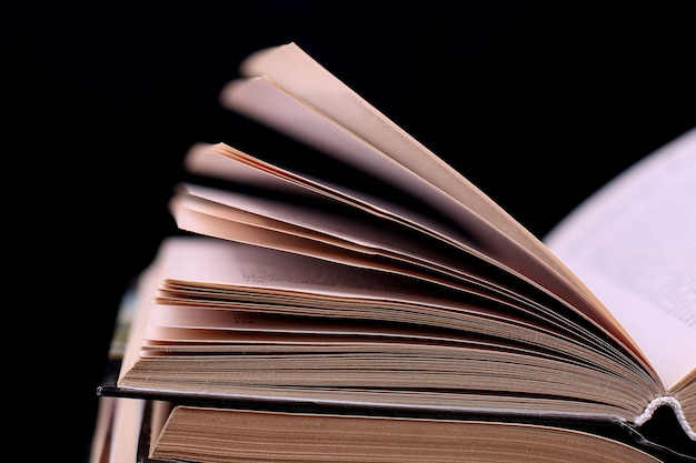 Open books are stacked on the desk on black, isolate. difficult homework at school, a mountain of knowledge.