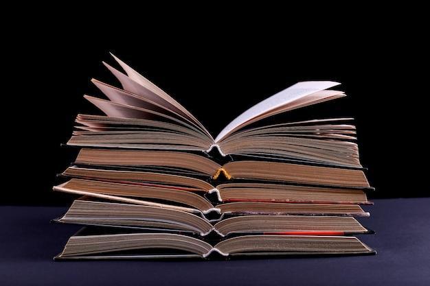 열린 책은 검은 배경에 책상에 쌓여 있으며 분리