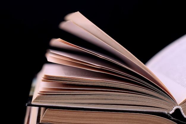 열린 책은 검은 색 책상 위에 쌓여 있습니다. 지식의 산 학교에서 어려운 숙제.