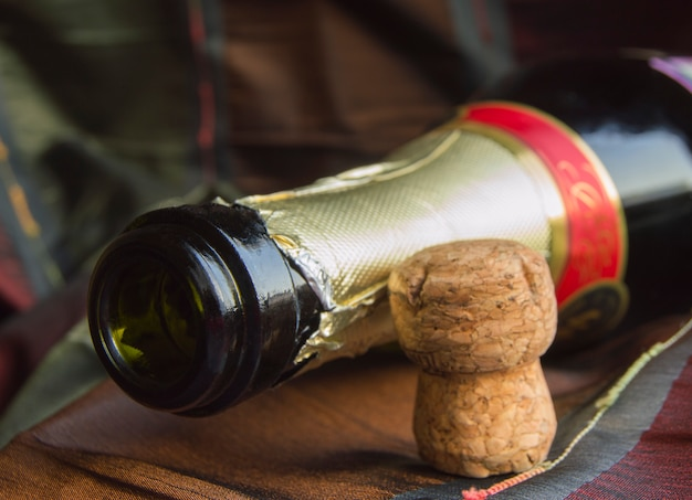 Open bottle of champagne and the cork on table with a tablecloth