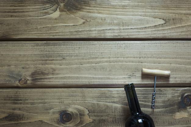Open bottle of red wine, corkscrew on a wooden board.