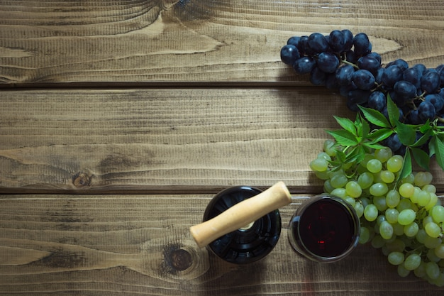 Open bottle of red wine with a glass, corkscrew and ripe grape on a wooden board.