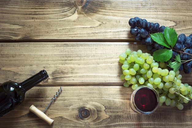 Open bottle of red wine with wineglass, corkscrew and ripe grape on wooden board.