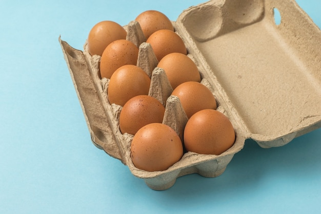 An open box of brown eggs on a blue surface. a natural product.