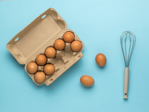 An open box of eggs and a whisk on a blue background. natural products and kitchen equipment.