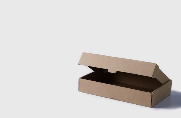 明るい背景に茶色の段ボールで作られたオープンボックスコピースペースのある低い商品の梱包と配送のための空のボックス